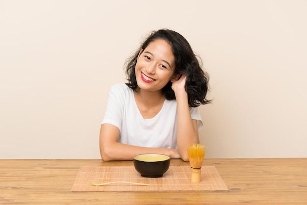 お茶抹茶を持つ若いアジアの女の子