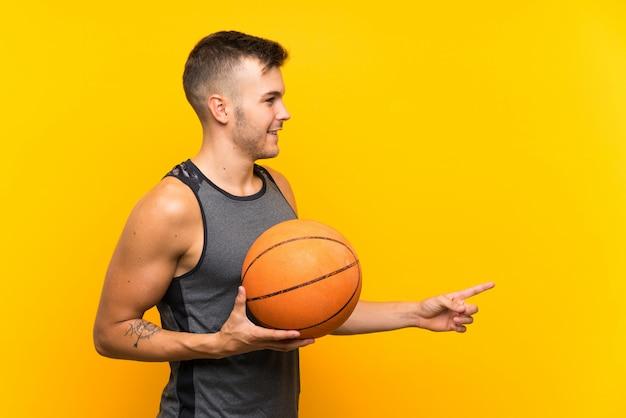 製品を提示する側を指している孤立した黄色の背景上にバスケットボールを保持している若いハンサムな金髪男