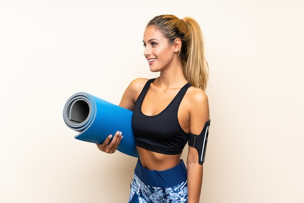 Молодая женщина спорта с ковриком на изолированном фоне