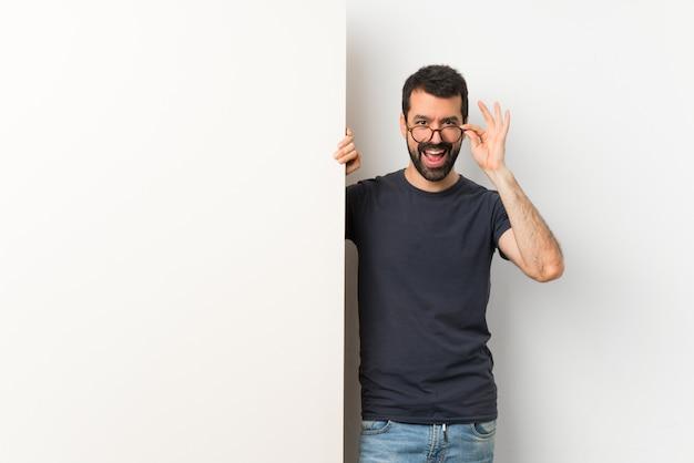 Молодой красивый мужчина с бородой держит большой пустой плакат с очками и улыбается