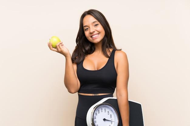 Молодая спортивная девушка с весами на изолированном фоне