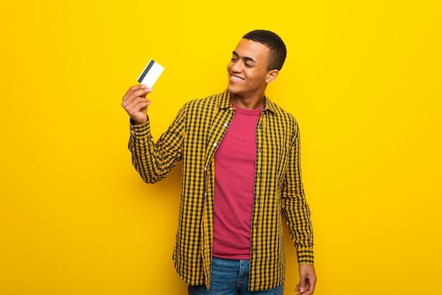 クレジットカードを保持していると考えて黄色の背景に若いアフロアメリカ人