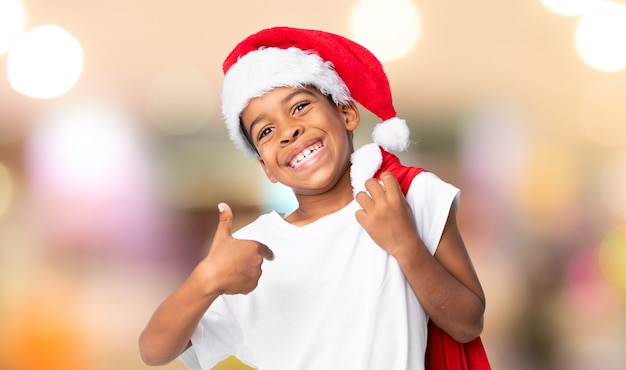 クリスマス帽子と背景をぼかした写真の上の贈り物の袋を取ってアフリカ系アメリカ人の少年