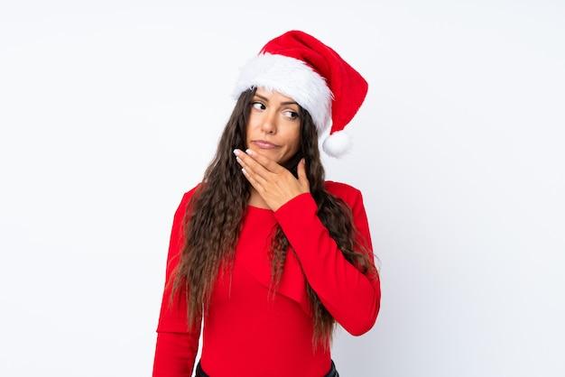 アイデアを考えて孤立した白い背景の上のクリスマス帽子の少女