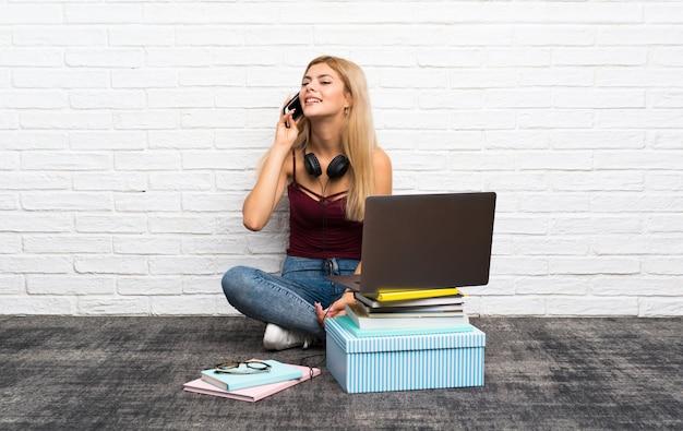 携帯電話との会話を維持する彼女のラップトップで床に座っているティーンエイジャーの女の子