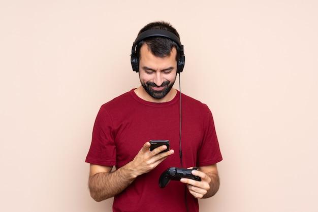 携帯電話でメッセージを送信する隔離された壁を越えてビデオゲームコントローラーで遊ぶ男