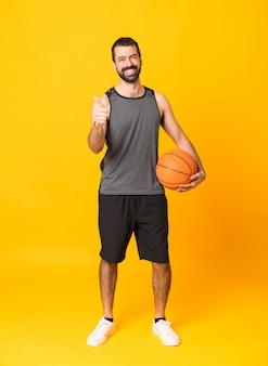 孤立した黄色の背景上のバスケットボールと親指アップと男の全身ショット