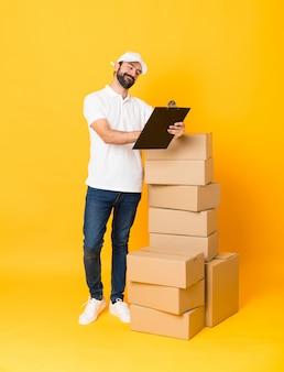 孤立した黄色の背景の上のボックスの中で配達人の全身ショット