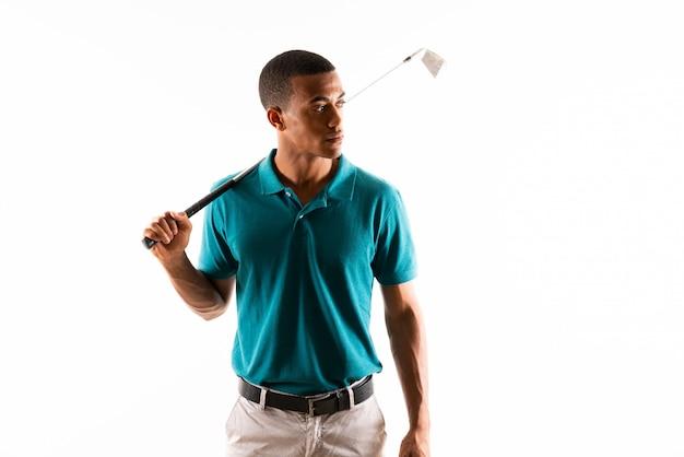 孤立した白い壁の上のアフロアメリカンゴルファープレーヤー男