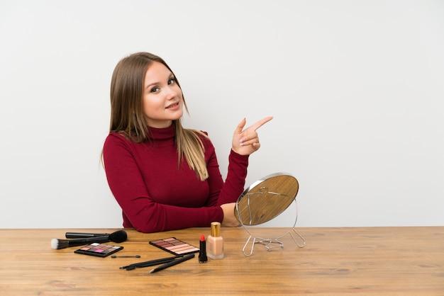 Девушка-подросток с палитрой макияжа и косметикой в столе, указывая пальцем в сторону