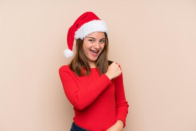 Молодая девушка в шляпе рождество над изолированной стеной празднует победу