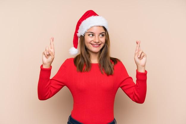 Молодая девушка в шляпе рождество над изолированной стеной с пересечением пальцев