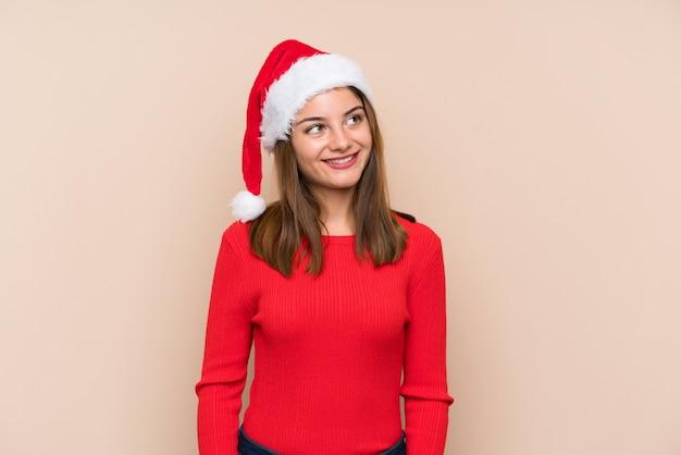 Молодая девушка в шляпе рождество над изолированной стеной, смеясь и глядя вверх