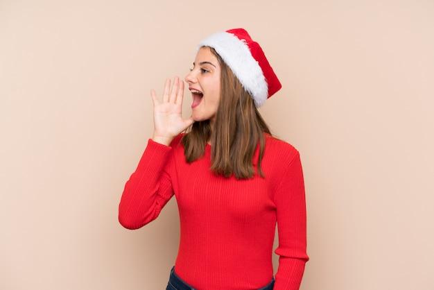 Молодая девушка в шляпе рождество над изолированной стеной, крича с широко открытым ртом