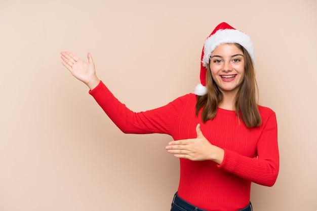 Молодая девушка в шляпе рождество над изолированной стеной, протягивая руки в сторону за приглашение прийти