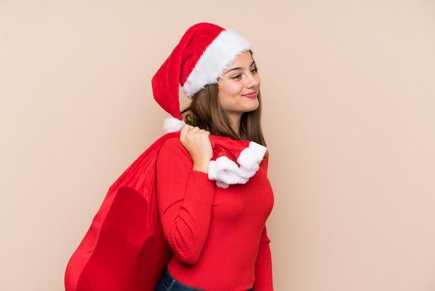 Молодая девушка в рождественской шапке на изолированной стене