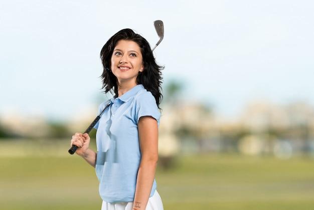 屋外で笑顔ながら見上げる若いゴルファーの女性