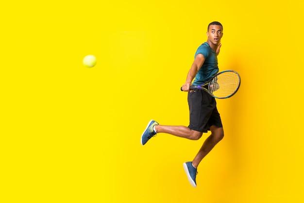 孤立した黄色の背景の上のアフロアメリカンテニスプレーヤー男