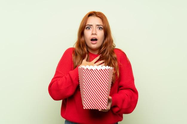 ポップコーンのボウルを保持している孤立した緑の背景の上のセーターとティーンエイジャーの赤毛の女の子
