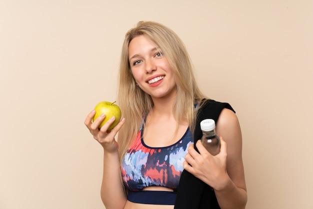 リンゴと水のボトルを持つ若いブロンドスポーツ女性