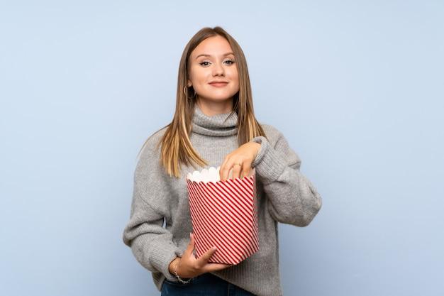 ポップコーンのボウルを保持しているセーターとティーンエイジャーの女の子