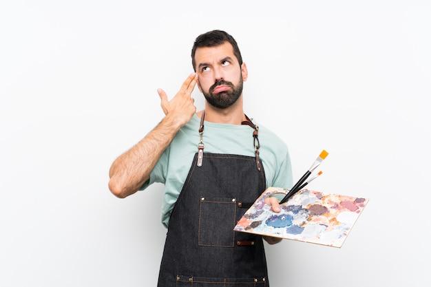 Молодой художник мужчина держит палитру с проблемами, делая жест самоубийства