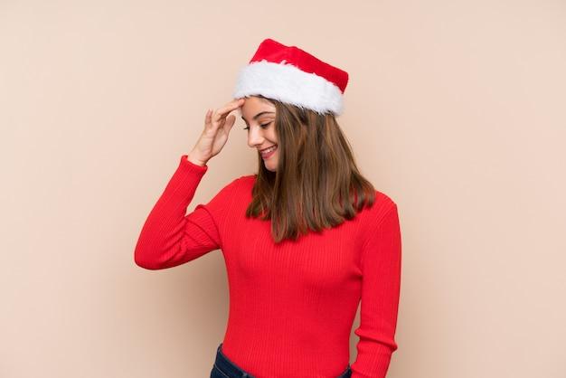 Молодая девушка с рождественской шляпой смеется