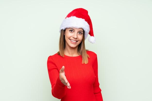 かなりの後に分離された緑のハンドシェーク上のクリスマス帽子の少女