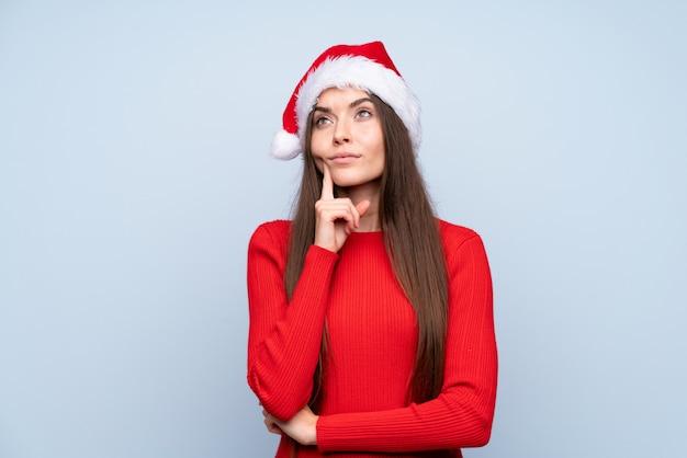 アイデアを考えて分離された青い上のクリスマス帽子の少女