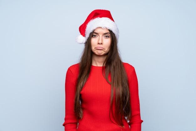Девушка с шляпой рождества над изолированным голубым унылым
