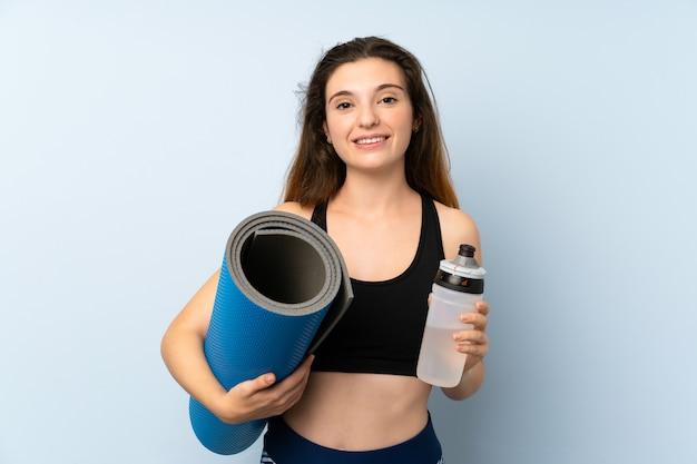 マットと孤立した壁の上の水のボトルを持つ若いブルネットの少女