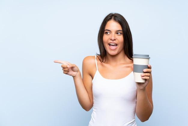 Молодая женщина, держащая прочь кофе на изолированной синей стене удивлен и указывая пальцем в сторону