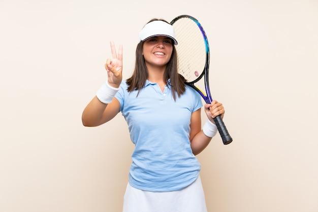 笑顔と勝利のサインを示す孤立した壁の上のテニスの若い女性