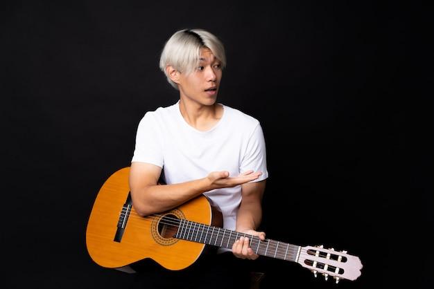 驚きの表情と黒の上のギターを持つ若いアジア男