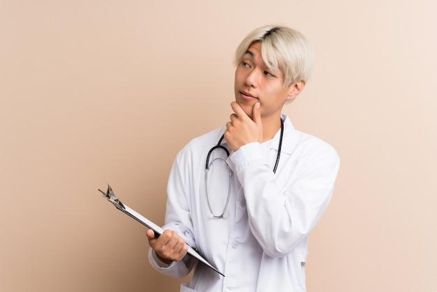 医者のガウンと考えながらフォルダーを保持している若いアジア人