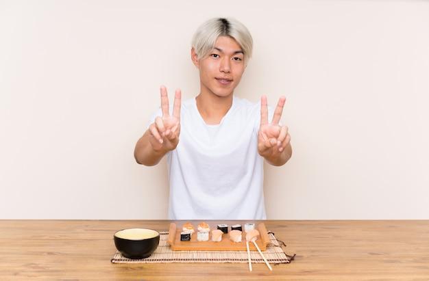 笑みを浮かべて、勝利のサインを示すテーブルで寿司と若いアジア人