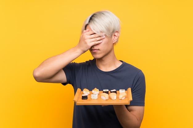 手で目を覆っている寿司と若いアジア人