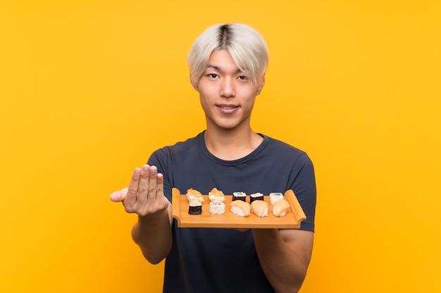 寿司を誘う若いアジア人男性