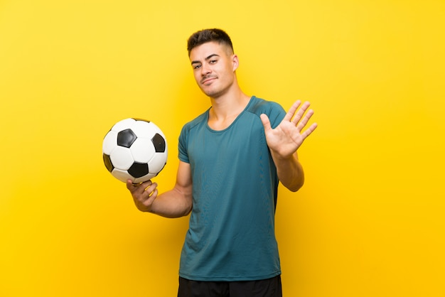 Красивый молодой футболист человек салютов с рукой с счастливым выражением