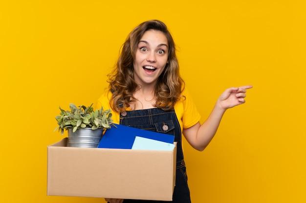 驚きと側を指して物事の完全なボックスを拾いながら移動を行う若いブロンドの女の子