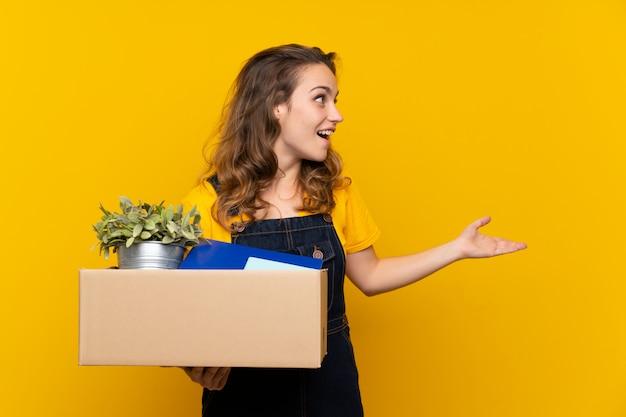 驚きの表情で物事の完全なボックスを拾いながら移動を行う若いブロンドの女の子
