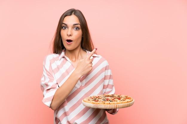 孤立したピンクの壁にピザをかざすと驚いて、側を指している若い女性