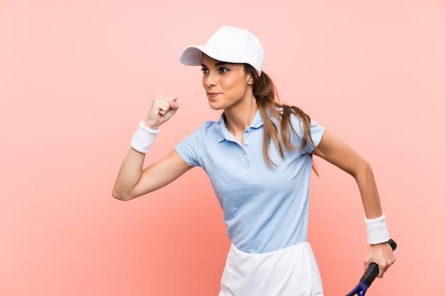孤立したピンクの壁の上の若いテニスプレーヤー女性