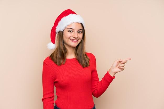 孤立した背景側に指を指す上のクリスマス帽子の少女