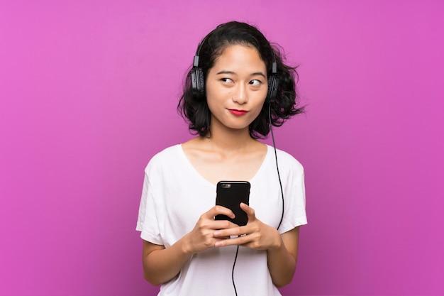 Музыка азиатской маленькой девочки слушая с чернью над изолированной фиолетовой стеной