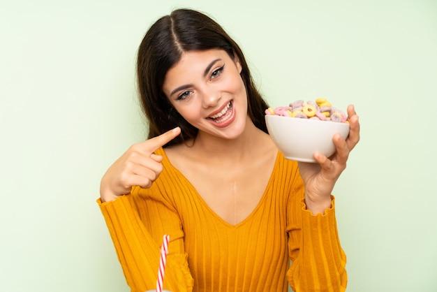 Счастливая девушка подростка имея завтрак с миской хлопьев