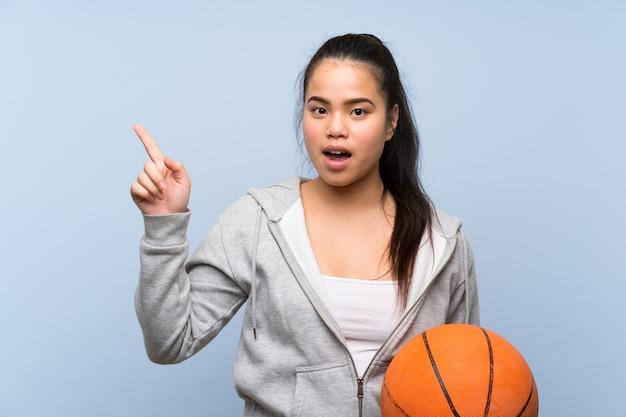 Молодая девушка играет в баскетбол удивлен и указывая пальцем в сторону