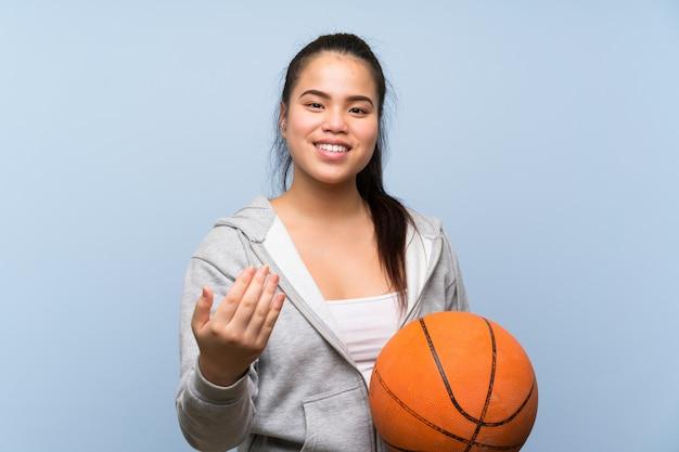 Молодая девушка играет в баскетбол, приглашая прийти с рукой. счастлив, что ты пришел