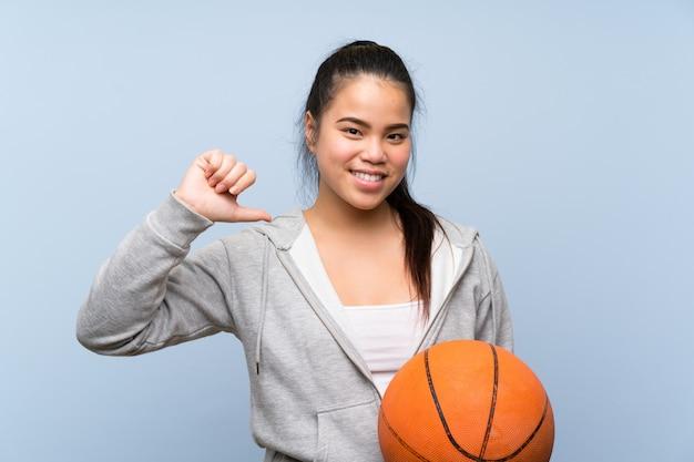Молодая девушка играет в баскетбол гордый и самодовольный