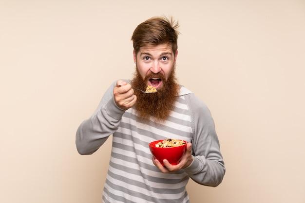 Рыжий мужчина с длинной бородой на изолированной стене, держа миску каши